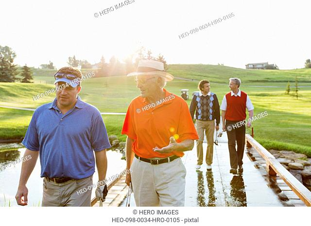 foursome of make golfers walking across bridge on fairway
