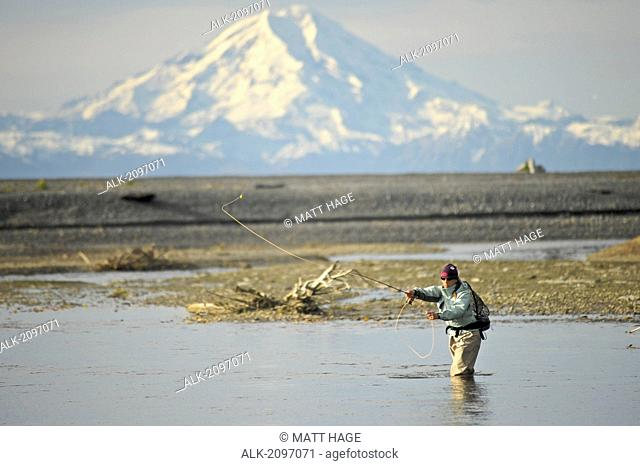 Woman Fly Fishing For Wild Steelhead On Deep Creek With Mt. Redoubt In The Background, Kenai Peninsula, Southcentral Alaska, Autumn