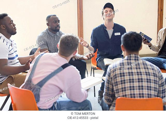 Men praying with bibles in prayer group circle
