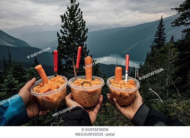 Canada, British Columbia, Yoho National Park, hikers holding rice dishes in plastic bowls