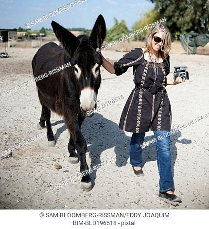 Caucasian woman walking with donkey