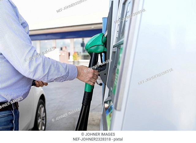 Hand holding petrol pump