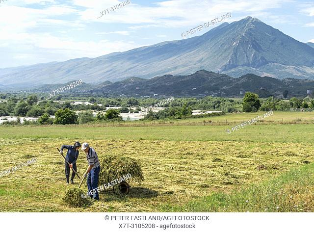 A couple harvesting fodder by the Drinos river with the Lunxheria mountains in the background, near Gjirokastra in southern Albania