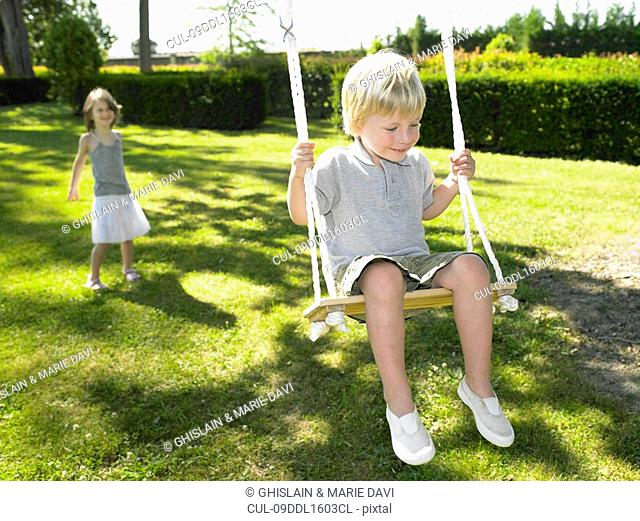 Boy on a swing, pushed by a girl