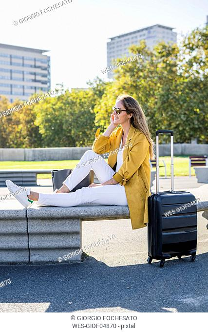 Smiling woman with suitcase sitting on a bench in the city