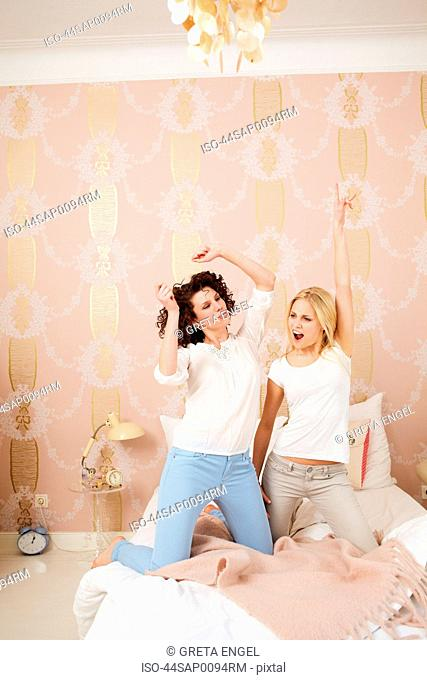 Women posing together on bed