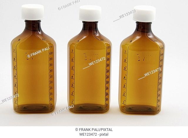 Three large brown medicine bottles on a white background