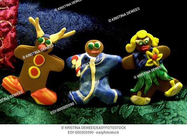 A trio of gingerbread people made from bakeable clay to be used as ornaments