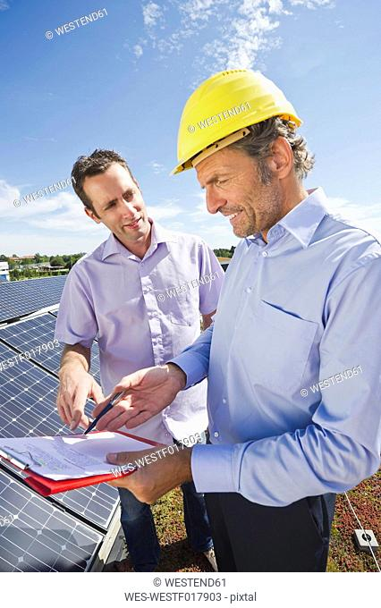 Germany, Munich, Man discussing with engineer in solar plant