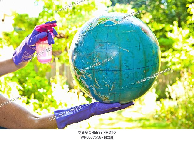 Woman wearing rubber gloves to clean globe outdoors
