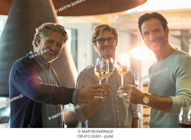 Portrait smiling men drinking white wine at winery