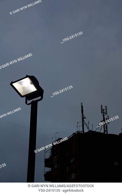 Security light on pole with high rise building at night in Rome Italy