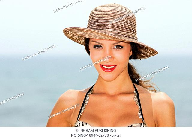 Close up portrait of a woman with a beautiful hat on a tropical beach