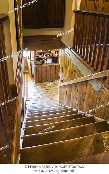 Looking down pinewood staircase from upper floor leading to entryway with wooden buffet inside an old 1835 fieldstone house