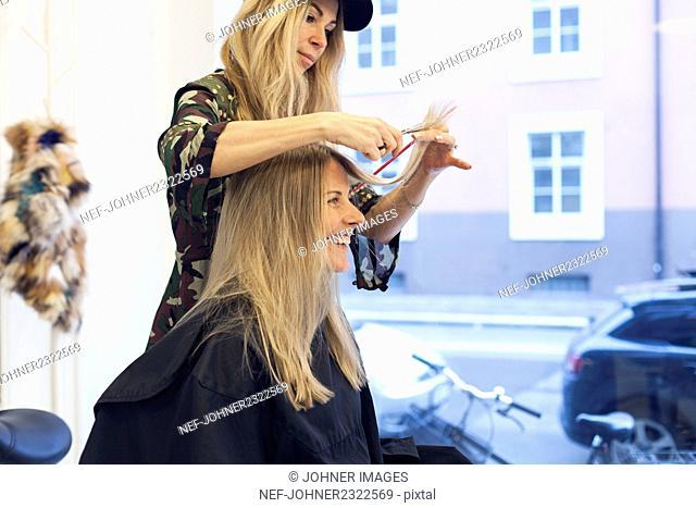 Blond woman cutting hair at hairdresser