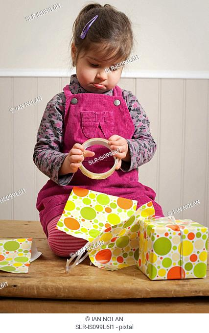 Little girl frowning as she wraps a gift
