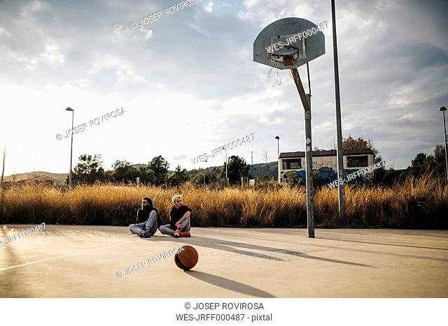 Two young men sitting on outdoor basketball court