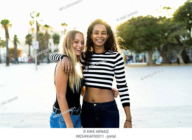 Portrait of two happy young women on square at sunset