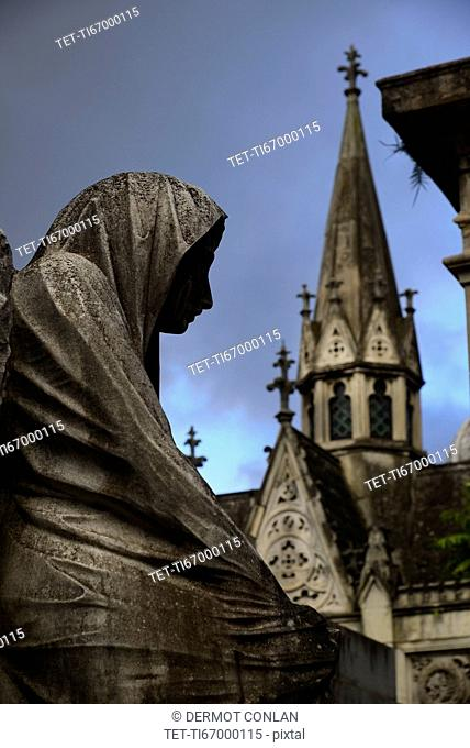 Close up of sculpture and church tower in Recoleta Cemetery