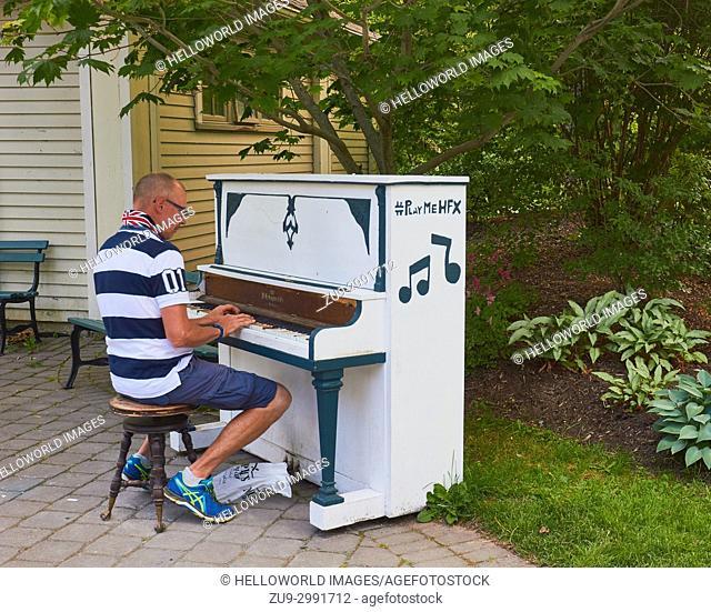 Man playing outdoor piano in Halifax Public Gardens, Halifax, Nova Scotia, Canada