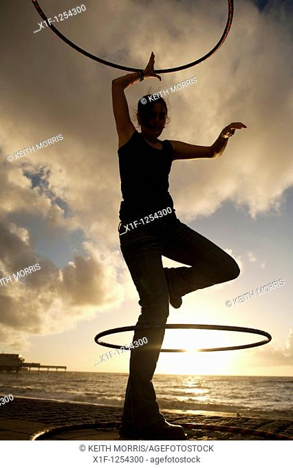A young woman student at Aberystwyth university using hoolah hoops at sunset, UK
