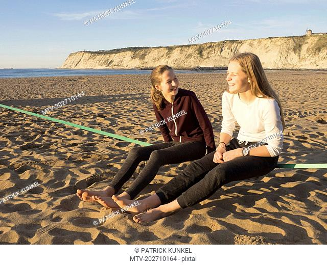 Teenage girls sitting on a slackline on a beach in Northern Spain