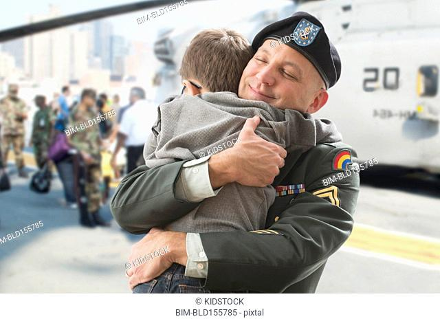 Caucasian returning soldier hugging son near helicopter