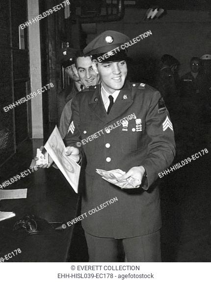 Sgt. Elvis A. Presley, 32nd Armored, 3rd Armored Div. collecting his last pay as he re-enters civilian life. March 5, 1960. - (BSLOC-2014-17-108)