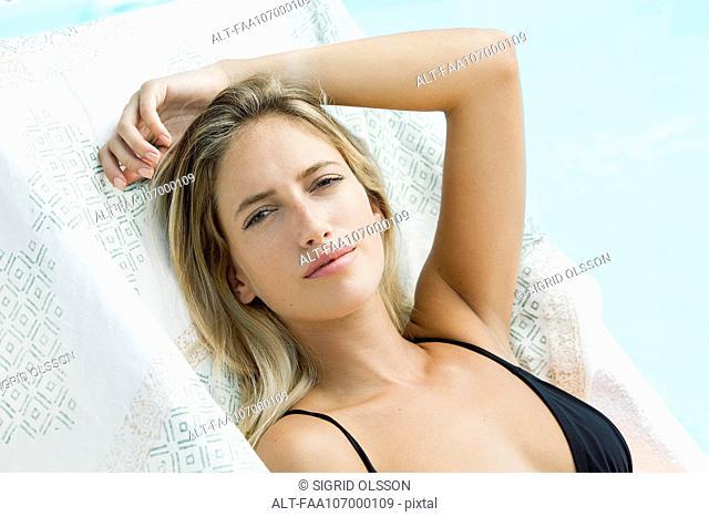 Woman relaxing by pool, portrait
