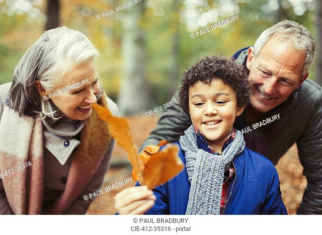 Grandparents and grandson holding autumn leaf