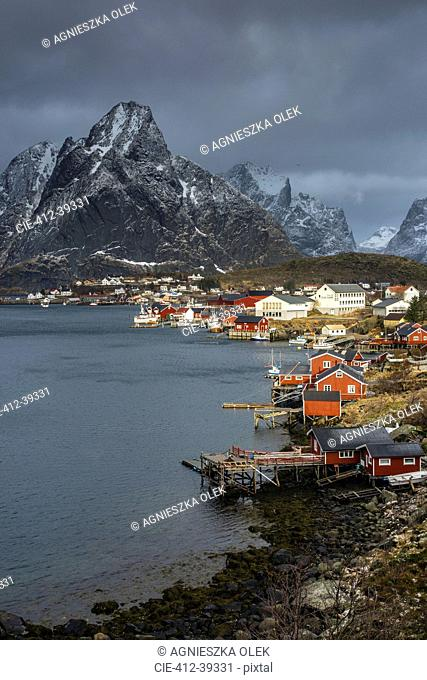 Fishing village at waterfront below rugged mountains, Reine, Lofoten, Norway
