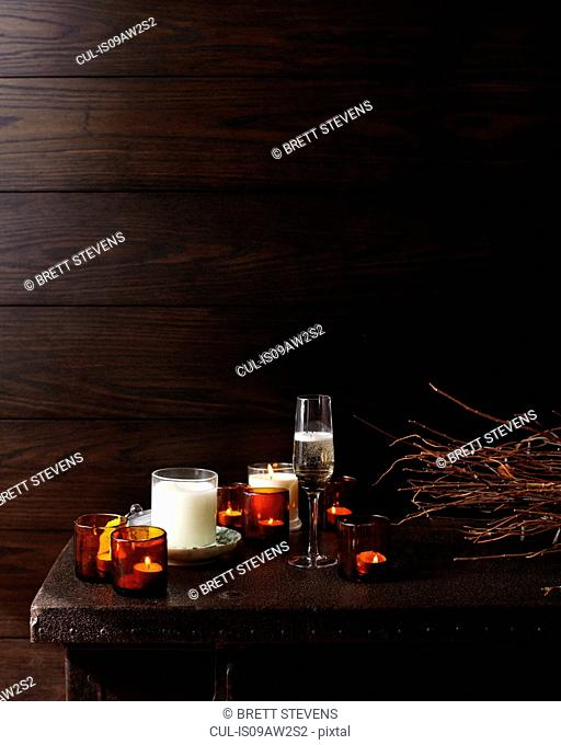 Wooden table with lit candles and glass of champagne