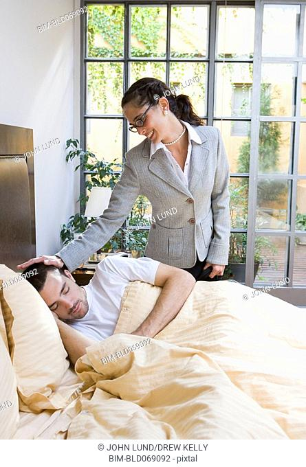 Businesswoman saying goodbye to man in bed