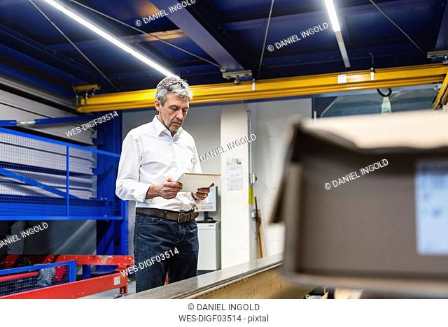 Businessman using tablet in production hall