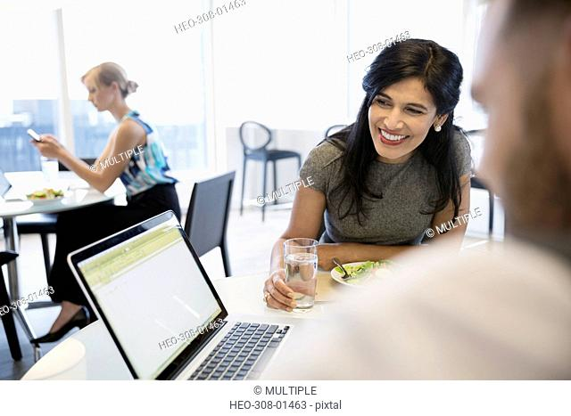 Smiling businesswoman using laptop with coworker eating lunch in office cafeteria