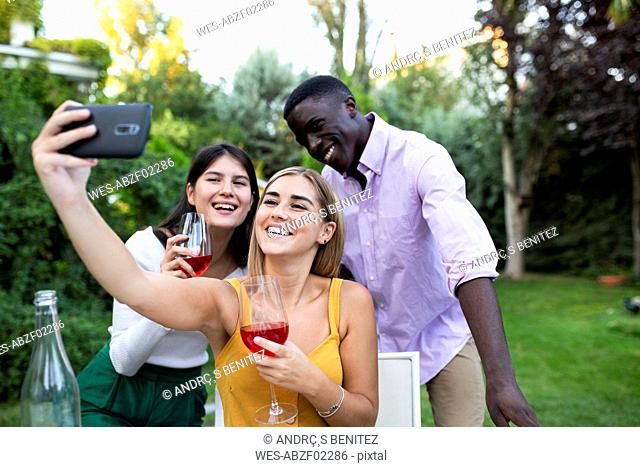 Friends having fun at a summer dinner in the garden, taking selfies