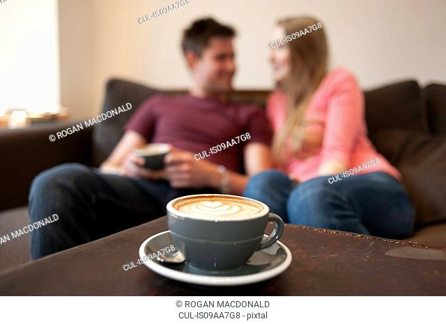 Young couple lounging on sofa in cafe