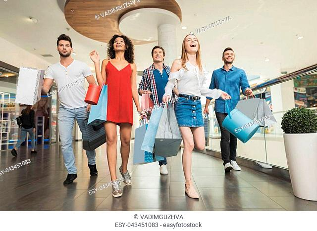 Sale in black Friday. The company of young people are engaged in shopping on a black Friday. Guys and girls are walking cheerfully along the shopping center...