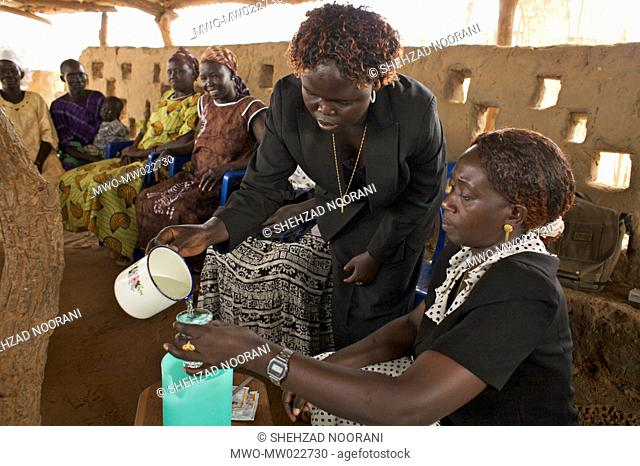 A Community Health Organizer CHO shows a group of women how to prepare Oral Rehabilitation Saline ORS, during a refresher's course for Community Health...