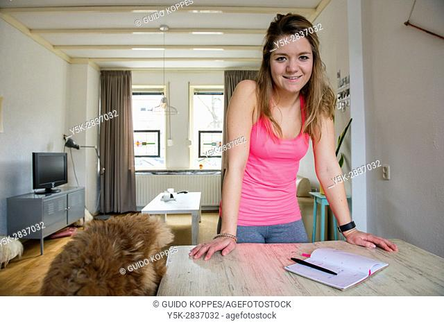 Tilburg, Netherlands. Young adult girly woman making an appointment using her manual, handwritten planner