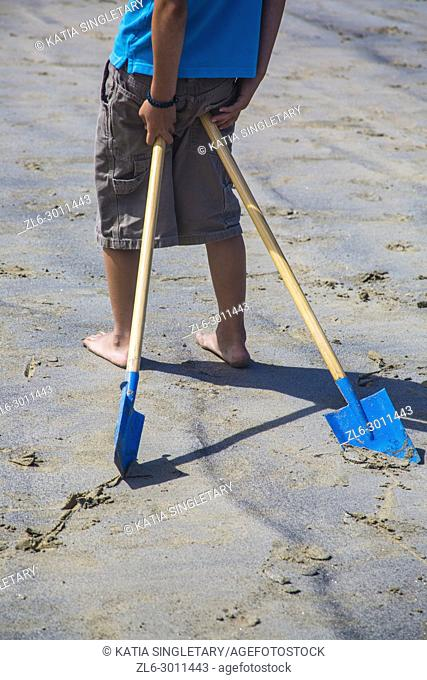 A man wearing shorts and a blue T-Shirt with two blue shovels resting on his behind,on a sandy beach in France