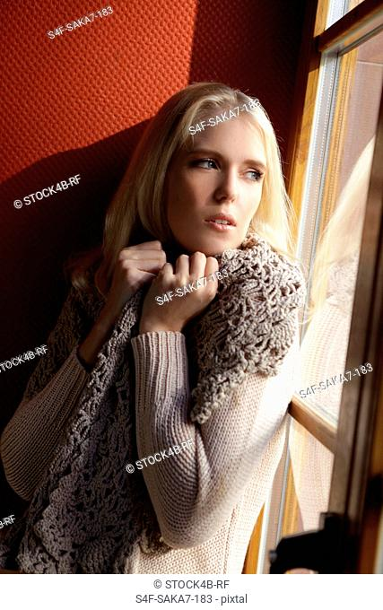 Serious young blond woman looking out of window