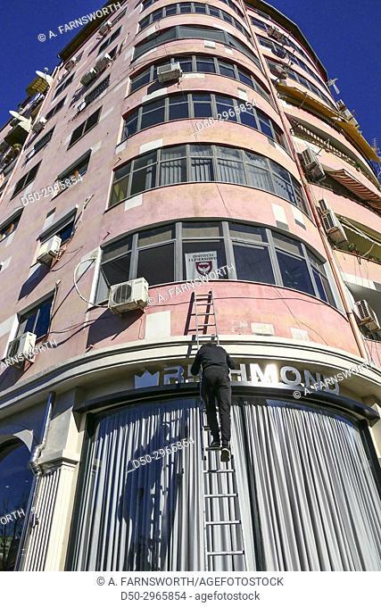 TIRANA, ALBANIA Worker on building facade