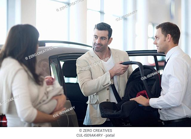 Mid adult couple with baby girl chatting about baby seat in car dealership