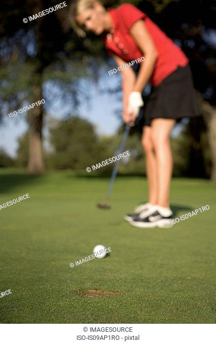 Young woman playing golf, defocussed
