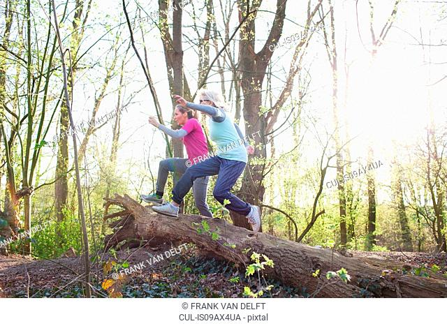 Side view of women in forest jumping over fallen tree