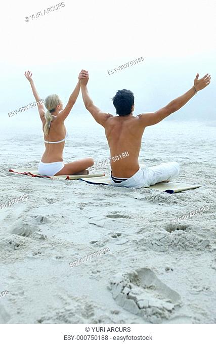 Rear view of a young couple practicing yoga by raising their hands at the beach