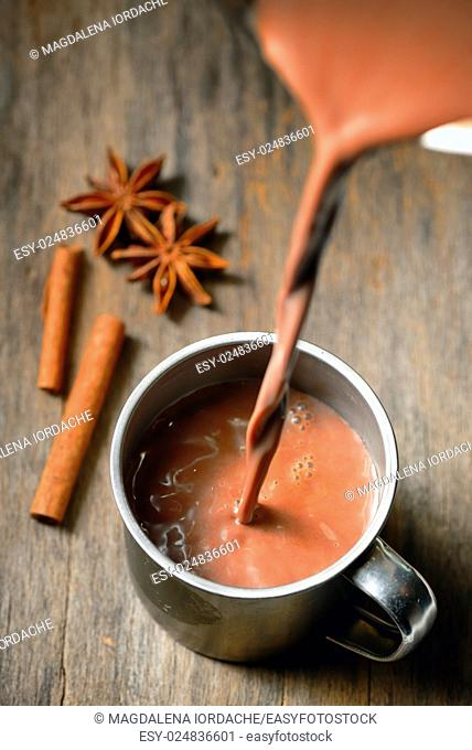 Hot chocolate with cinnamon stick on wooden table