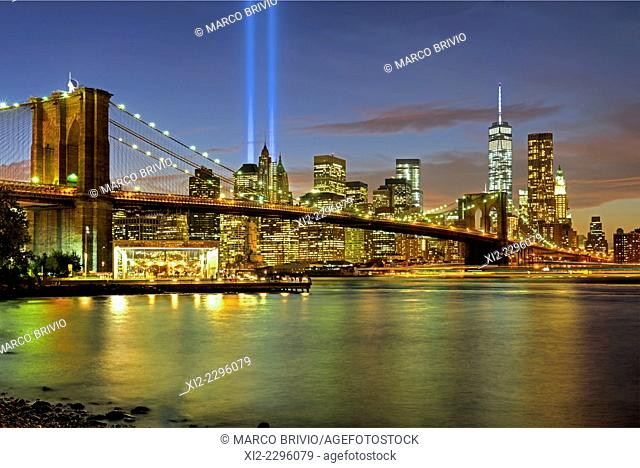 The Brooklyn bridge and Manhattan skyline at sunset, On September 11th, two blue beams (Tribute in Light) are the homage to the victims of 9-11-2011 attack to...