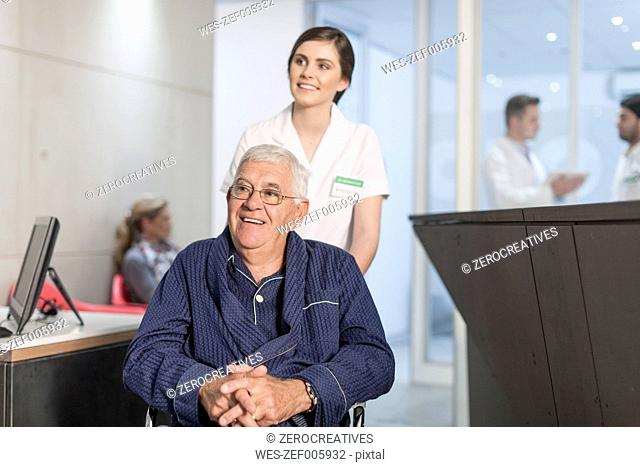 Nurse with patient in wheelchair at clinic reception